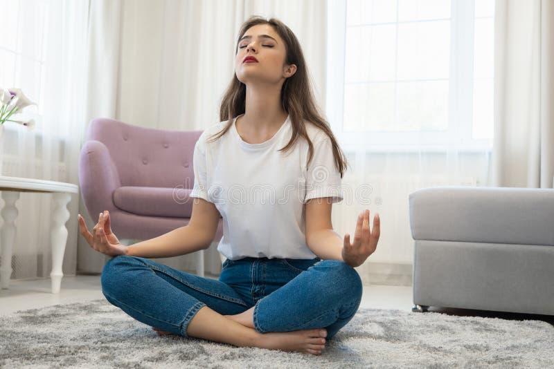 Mooie jonge donkerbruine vrouw die jeans en witte t-shirtzitting op de vloer in de positie van de asanayoga in helder dragen royalty-vrije stock afbeelding