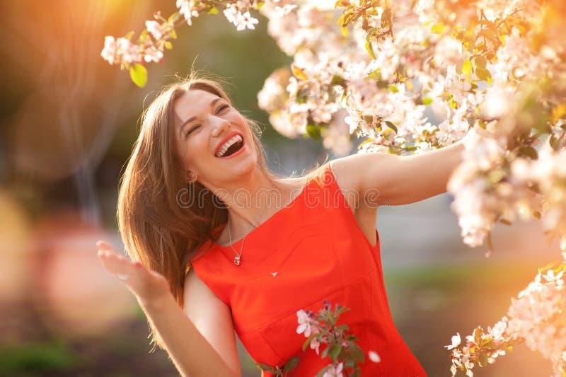Mooie jonge donkerbruine vrouw die zich dichtbij de bloeiende boom bevinden stock fotografie