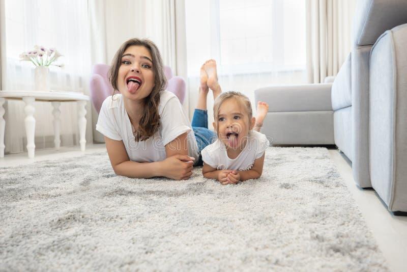 Mooie jonge donkerbruine vrouw met leuk babymeisje die jeans en witte t-shirts dragen die op de vloer in helder liggen stock afbeeldingen