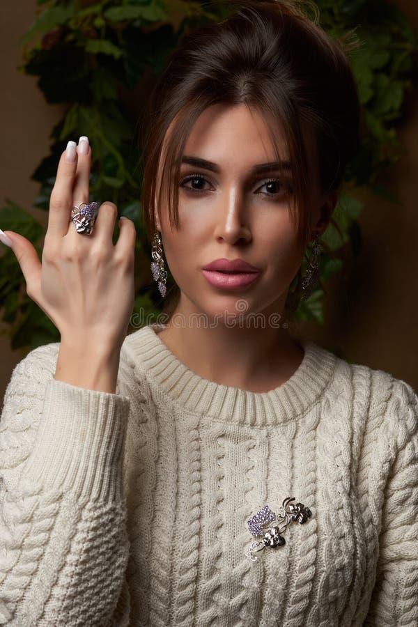Mooie jonge donkerbruine vrouw in warme gebreide witte sweater royalty-vrije stock foto's