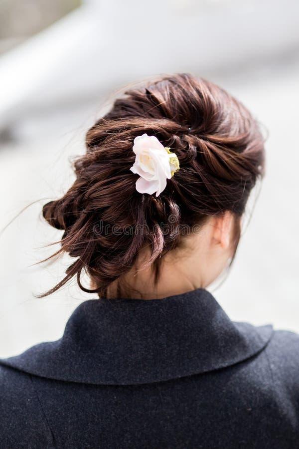 Mooie jonge donkere haired vrouw met creatief vlechtkapsel met een bloem stock afbeeldingen