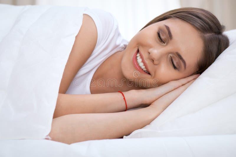 Mooie jonge en gelukkige vrouwenslaap terwijl het liggen in bed die comfortabel en gelukzalig glimlachen royalty-vrije stock foto's