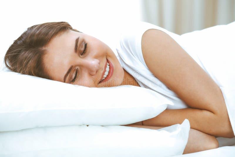 Mooie jonge en gelukkige vrouwenslaap terwijl het liggen in bed die comfortabel en gelukzalig glimlachen stock foto's