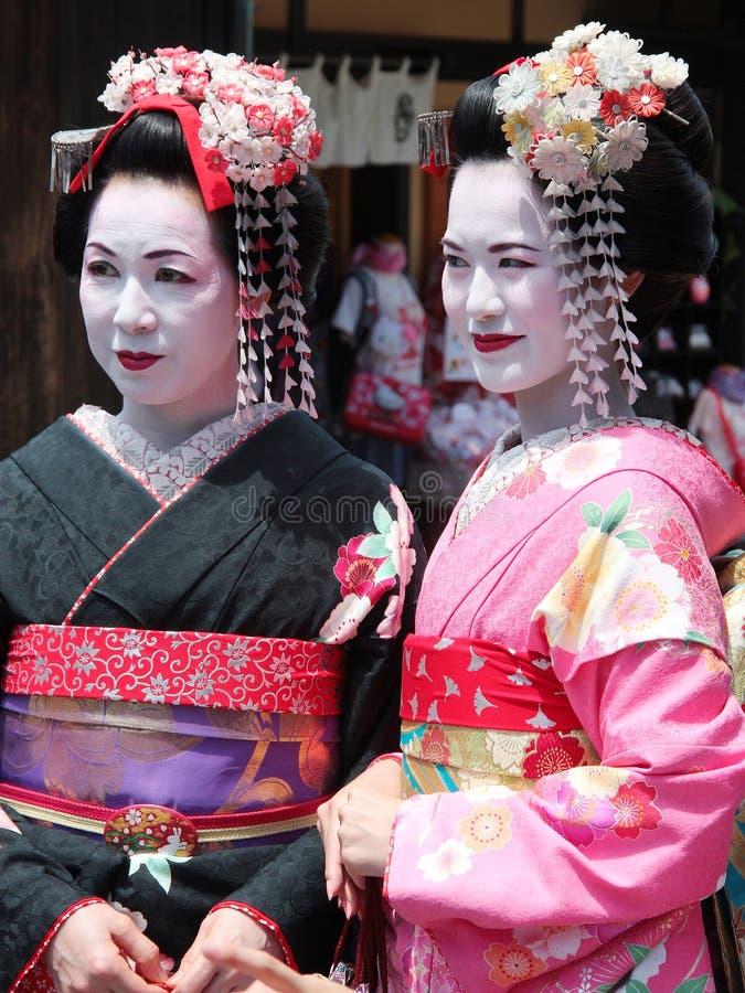 Mooie jonge en rijpe geisha die in van de de stadsgeisha van Kyoto het oude district Japan lopen royalty-vrije stock foto