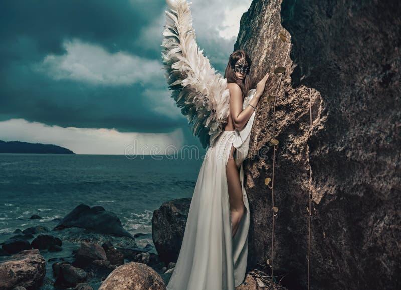 Mooie jonge engel die op clif beklimmen stock foto