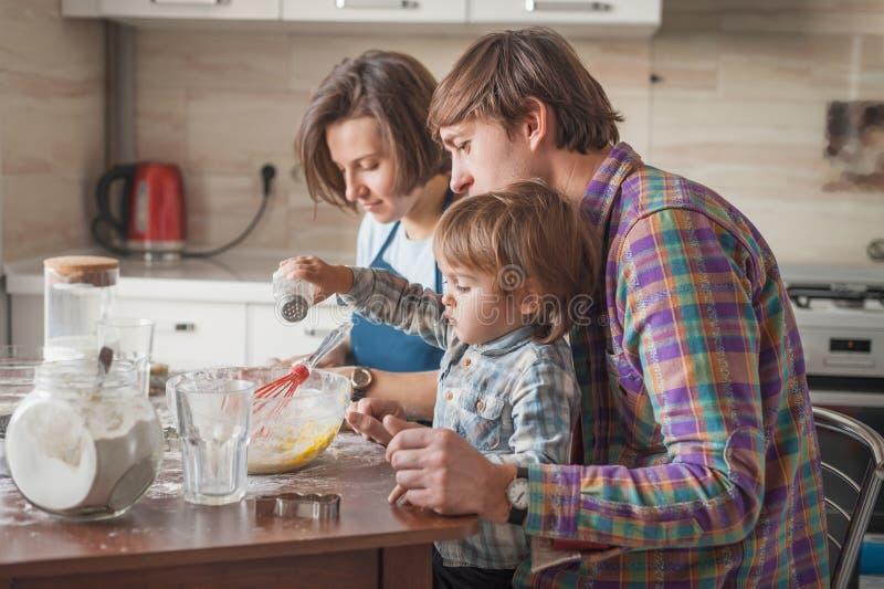 mooie jonge familie die deeg maken stock afbeelding
