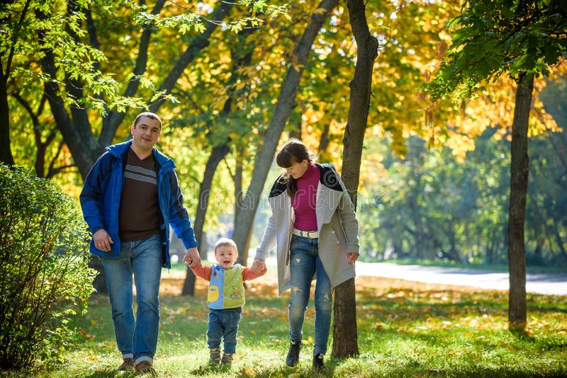 Mooie jonge familie op een gang in de herfstbos op esdoornyello royalty-vrije stock afbeeldingen