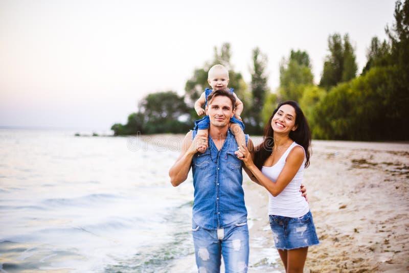 Mooie jonge familie op vakantie met baby De vader houdt het blondemeisje in haar wapens, en de donkerbruine moeder van ` s koeste stock fotografie