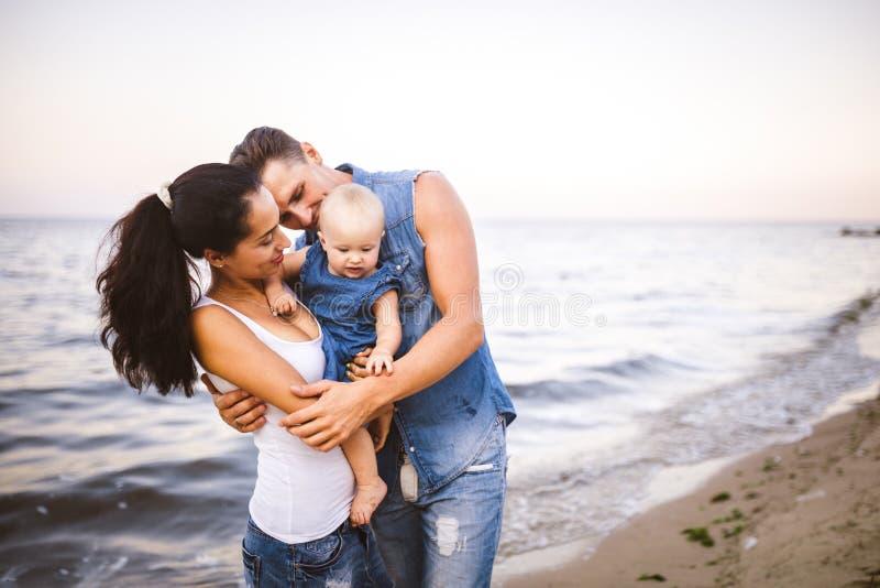 Mooie jonge familie op vakantie met baby De vader houdt het blondemeisje in haar wapens, en de donkerbruine moeder van ` s koeste royalty-vrije stock foto's