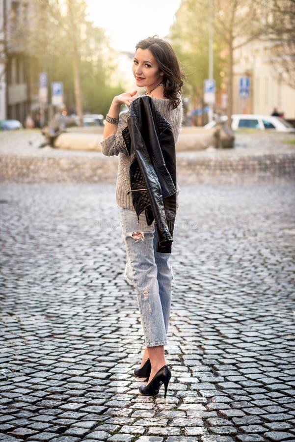 Mooie jonge gelukkige vrouw die op de straat lopen stock fotografie