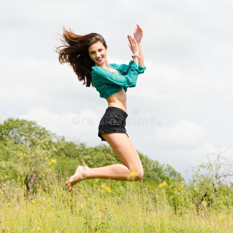 Mooie jonge gelukkige vrouw die & in openlucht op de zomerdag dansen springen royalty-vrije stock afbeeldingen