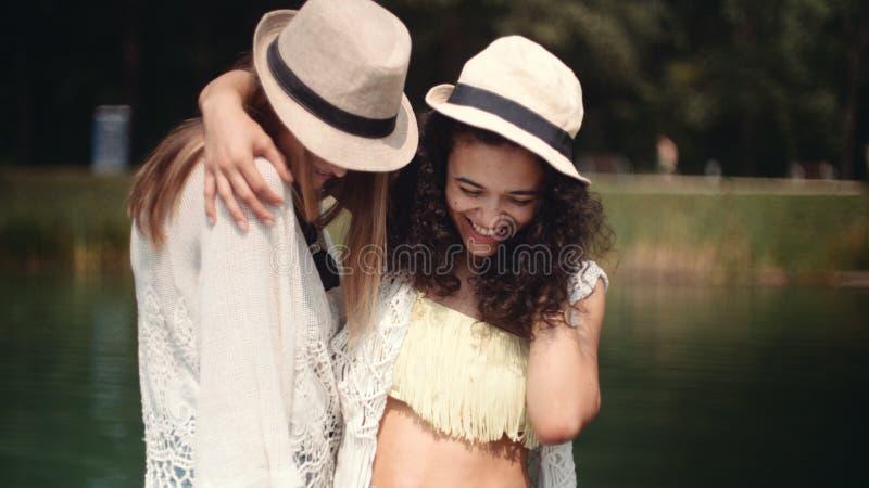 Mooie jonge gemengde rasmeisjes die dichtbij meer spreken en van vakantie genieten stock afbeeldingen