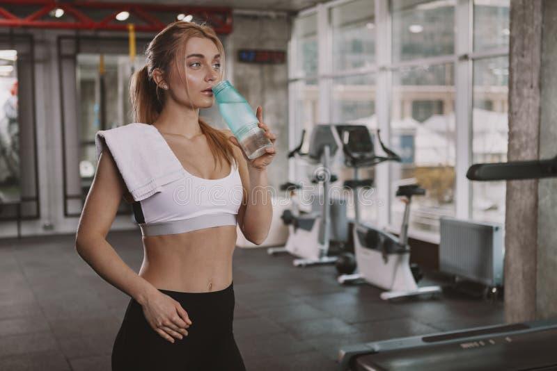 Mooie jonge geschiktheidsvrouw die bij de gymnastiek uitwerken stock fotografie