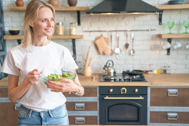 Mooie jonge glimlachende vrouw die groene salade in de keuken houden Zijdelings het kijken Gezond voedsel Plantaardige salade Die royalty-vrije stock foto's