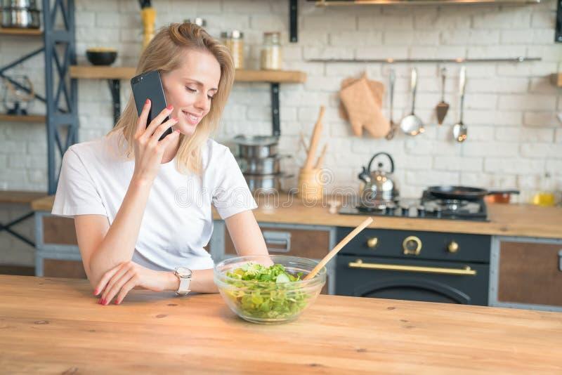 Mooie jonge glimlachende vrouw die op de telefoon spreken terwijl het maken van salade in de keuken Gezond voedsel Plantaardige s stock afbeelding