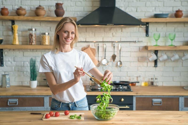 Mooie jonge glimlachende vrouw die salade in de keuken maken Gezond voedsel Plantaardige salade Dieet Gezonde Levensstijl Thuis h royalty-vrije stock fotografie