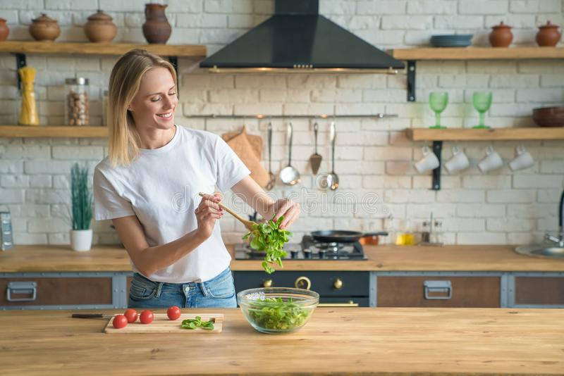 Mooie jonge glimlachende vrouw die salade in de keuken maken Gezond voedsel Plantaardige salade Dieet Gezonde Levensstijl Thuis h royalty-vrije stock foto's