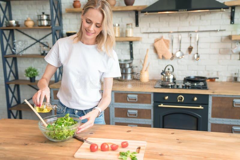 Mooie jonge glimlachende vrouw die salade in de keuken maken Gezond voedsel Plantaardige salade Dieet Gezonde Levensstijl Thuis h royalty-vrije stock foto