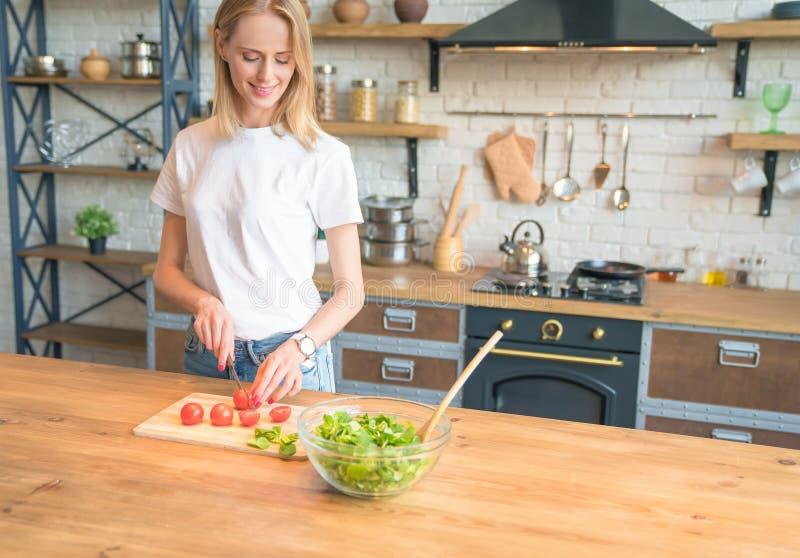 Mooie jonge glimlachende vrouw die salade in de keuken maken Scherpe Tomaten Gezond voedsel Plantaardige salade Dieet Gezond royalty-vrije stock afbeeldingen