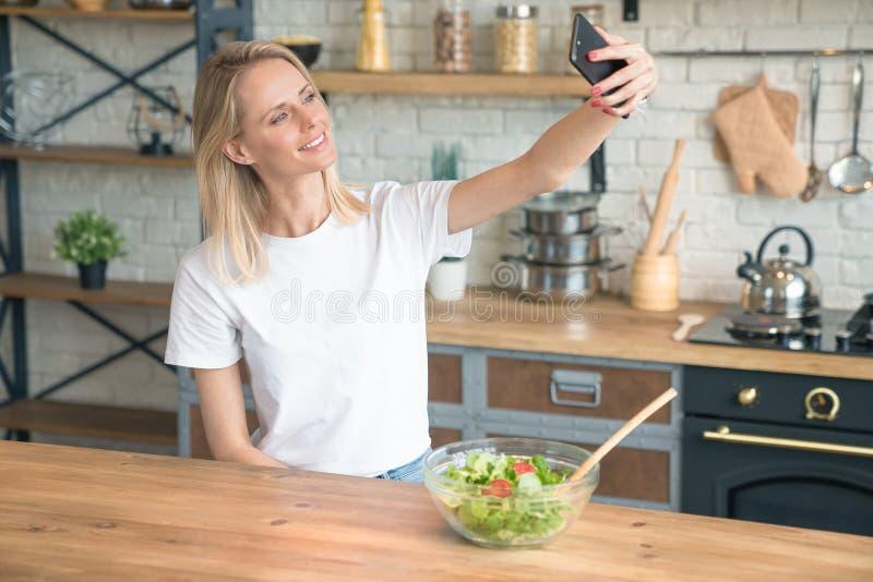 Mooie jonge glimlachende vrouw die selfie met de telefoon maken terwijl het maken van salade in de keuken Gezond voedsel Plantaar stock foto