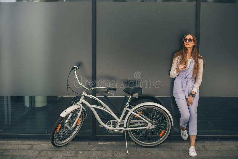 Mooie jonge glimlachende vrouw die zich dichtbij haar uitstekende fiets bevinden royalty-vrije stock afbeelding