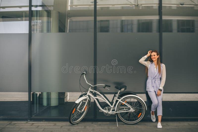 Mooie jonge glimlachende vrouw die zich dichtbij haar uitstekende fiets bevinden royalty-vrije stock foto