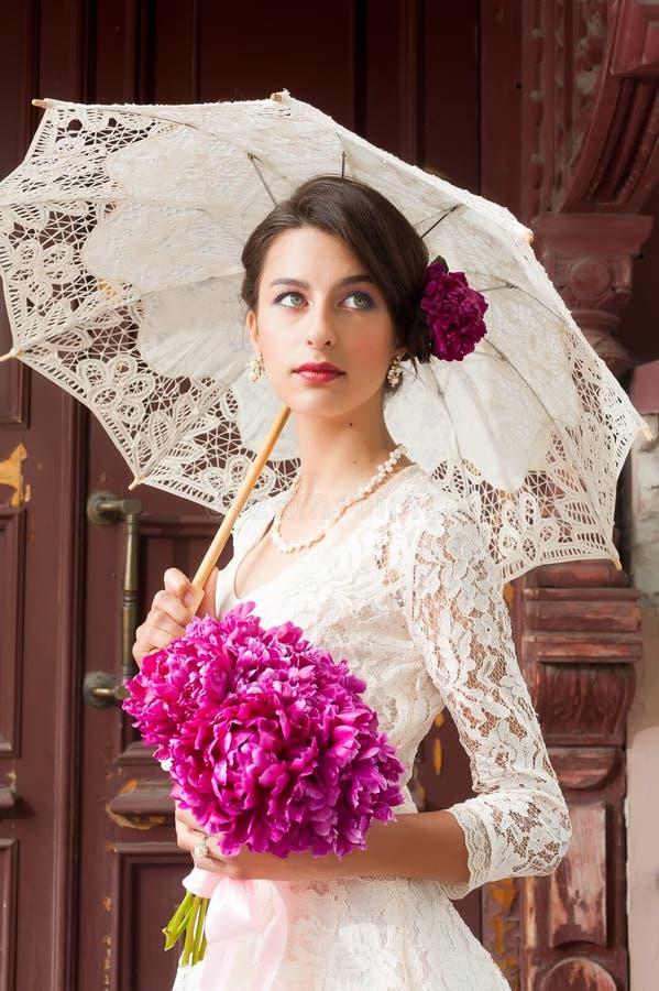 Mooie jonge glimlachende vrouw met bloemen royalty-vrije stock afbeelding