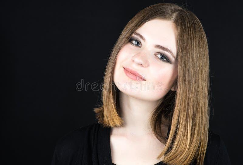 Mooie jonge glimlachende vrouw op zwarte achtergrond stock fotografie