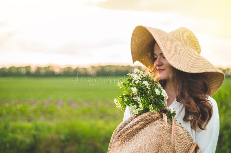 Mooie jonge glimlachende vrouw in uitstekende kleding en strohoed in gebiedswildflowers Het meisje houdt een mand met bloemen stock afbeelding