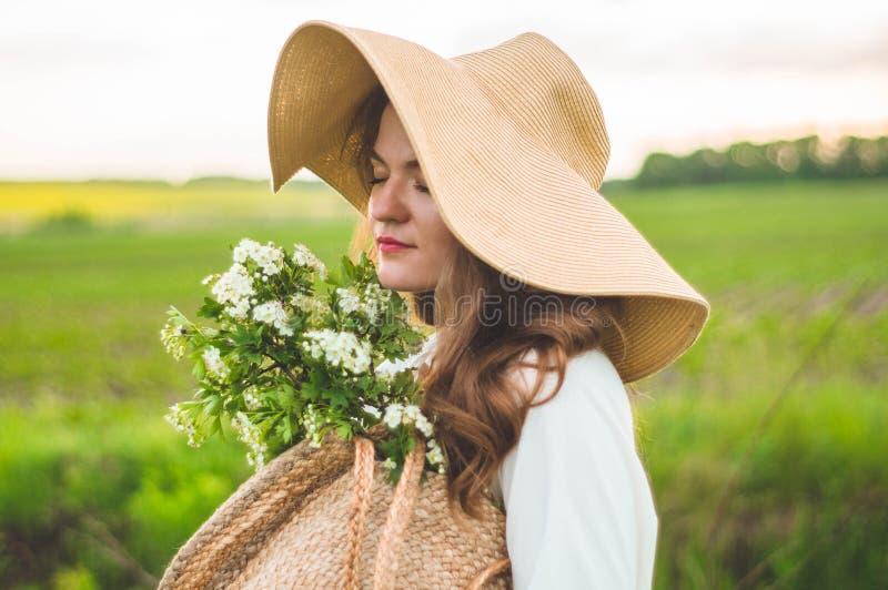 Mooie jonge glimlachende vrouw in uitstekende kleding en strohoed in gebiedswildflowers Het meisje houdt een mand met bloemen stock afbeeldingen