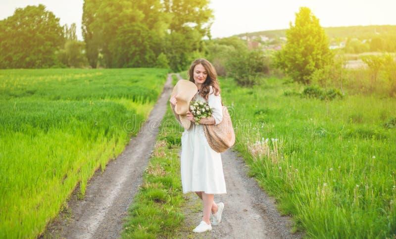 Mooie jonge glimlachende vrouw in uitstekende kleding en strohoed in gebiedswildflowers Het meisje houdt een mand met bloemen stock foto's