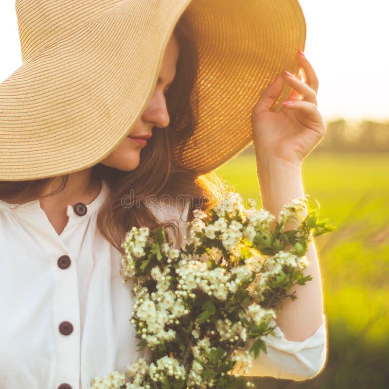 Mooie jonge glimlachende vrouw in uitstekende kleding en strohoed in gebiedswildflowers Het meisje houdt een mand met bloemen royalty-vrije stock afbeelding