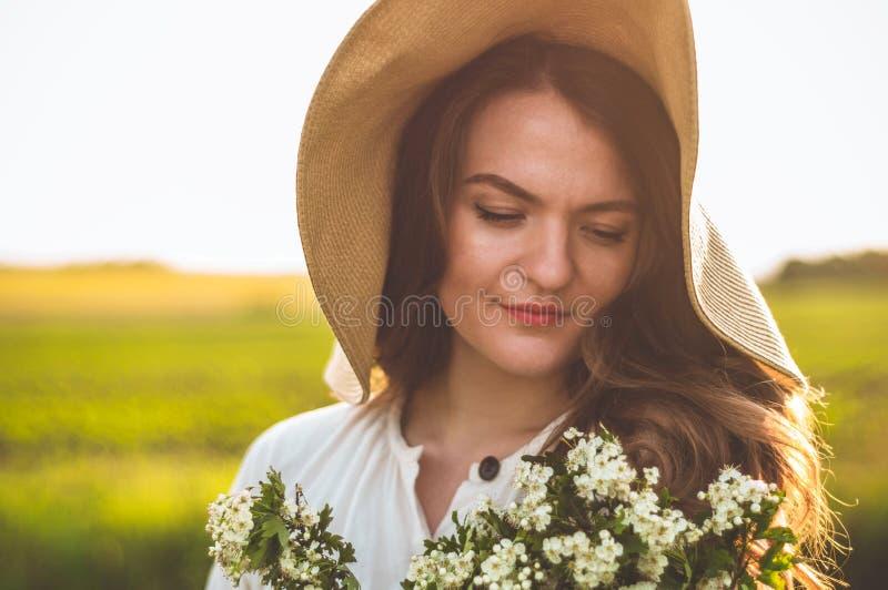 Mooie jonge glimlachende vrouw in uitstekende kleding en strohoed in gebiedswildflowers Het meisje houdt een mand met bloemen royalty-vrije stock foto