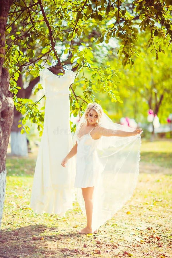 Mooie jonge het blondebruid van de ochtendbruid in de tuin die haar sluier, huwelijkskleding het hangen op een boom bekijken, sel stock afbeeldingen