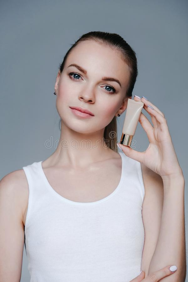 Mooie jonge het gezichtsroom van de vrouwenholding Gezichtsbehandeling De kosmetiek, schoonheid en kuuroord royalty-vrije stock foto
