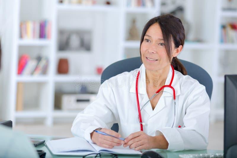 Mooie jonge het glimlachen vrouwelijke artsenzitting bij bureau stock fotografie