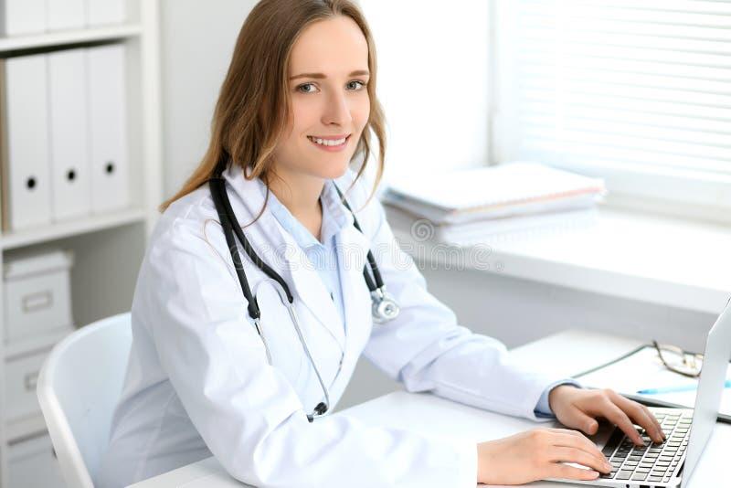 Mooie jonge het glimlachen vrouwelijke artsenzitting bij de lijst dichtbij venster in het ziekenhuis royalty-vrije stock afbeelding