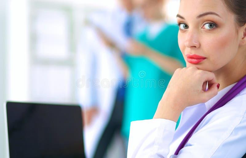 Mooie jonge het glimlachen vrouwelijke artsenzitting bij het bureau stock afbeeldingen