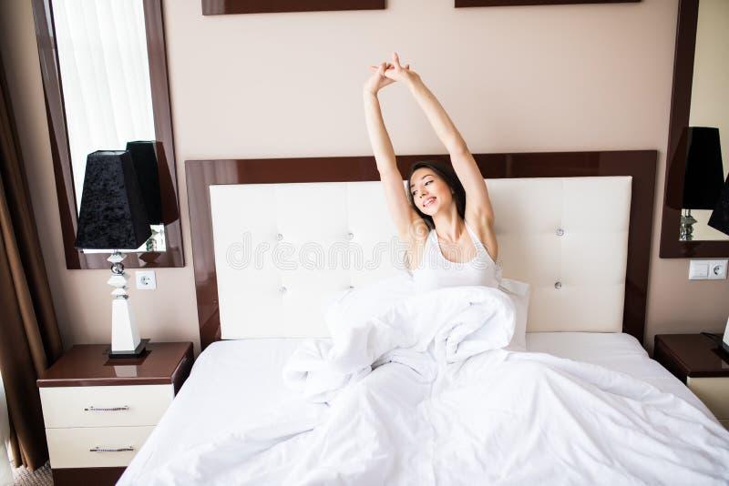Mooie jonge het glimlachen vrouwenzitting op bed en het uitrekken zich in de ochtend bij slaapkamer stock fotografie