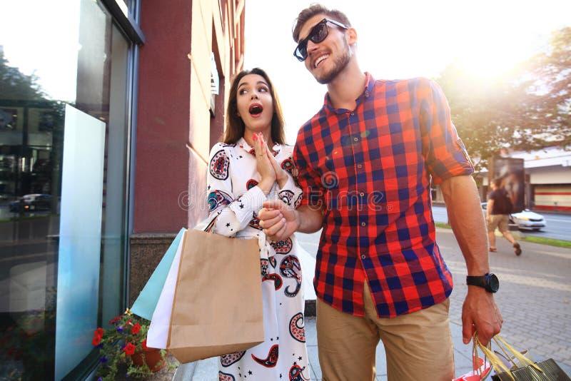 Mooie jonge het houden van paar dragende het winkelen zakken en samen van het genieten royalty-vrije stock afbeelding