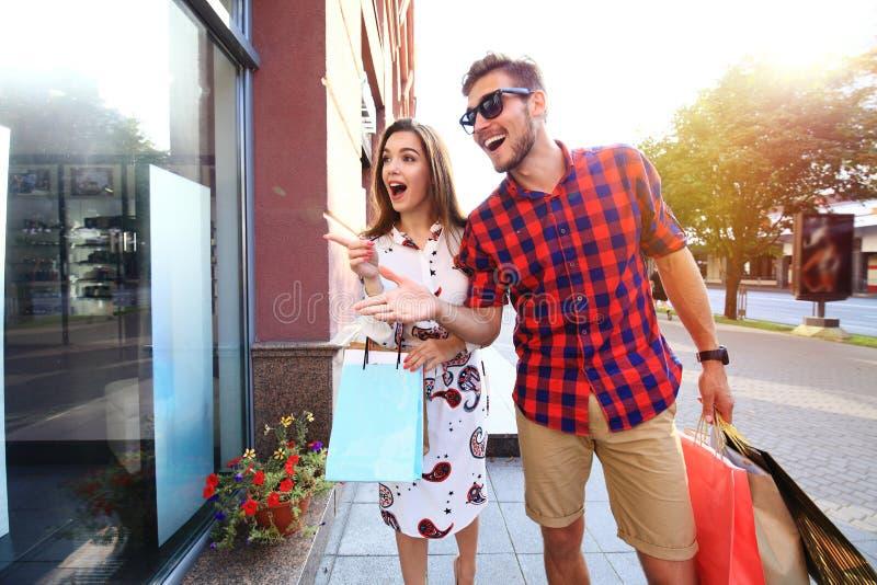 Mooie jonge het houden van paar dragende het winkelen zakken en samen van het genieten royalty-vrije stock foto's