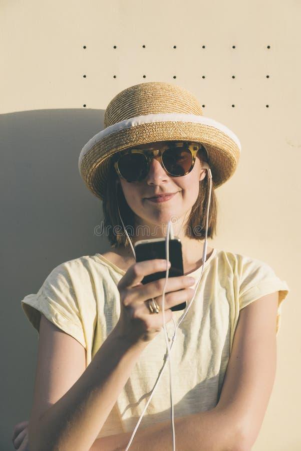 Mooie jonge hipster Kaukasische vrouw met smartphone en earp stock foto's