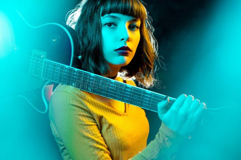 Mooie jonge hipstervrouw met krullend haar met rode gitaar in neonlichten De musicus van de rots speelt elektrogitaar stock afbeeldingen