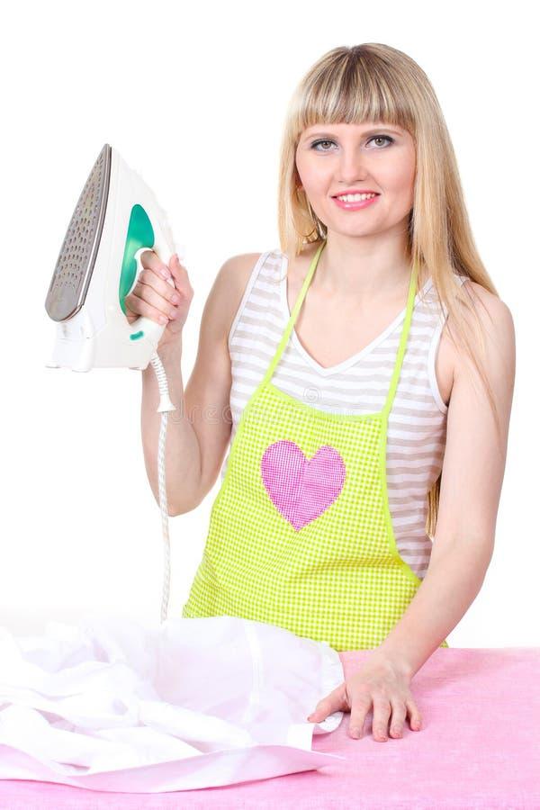 Mooie jonge huisvrouw met ijzer stock foto