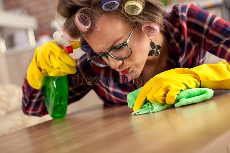 Mooie jonge huisvrouw met krulspeld die huiskarweien doen stock foto