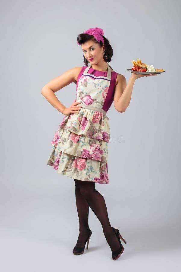 Mooie jonge huisvrouw in purpere kleding en schort met dessert royalty-vrije stock afbeelding