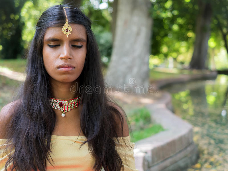 Mooie jonge Indische vrouw het praktizeren meditatie in het park stock foto's