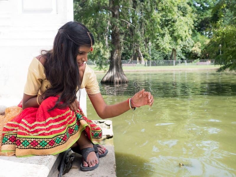 Mooie jonge Indische vrouwenzitting en het spelen bij het meer sid royalty-vrije stock foto