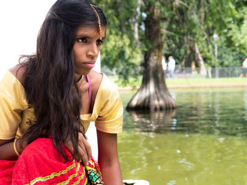 Mooie jonge Indische vrouwenzitting en het spelen bij het meer sid stock foto
