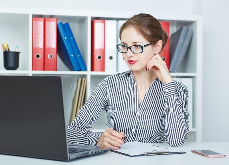 Mooie jonge Kaukasische onderneemster die aan laptop in het bureau werken Zaken, uitwisselingsmarkt, baanaanbieding royalty-vrije stock fotografie